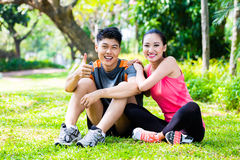 Asian couple having break at during sport training Stock Photo