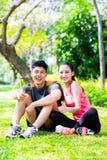 Asian couple having break at during sport training Stock Image