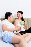 Asian couple having breakfast in bedroom Stock Photos