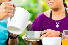 Asian couple having coffee on home porch Stock Photos