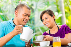 Asian couple having coffee on home porch Royalty Free Stock Image