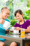 Asian couple having coffee on home porch Royalty Free Stock Photos
