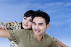 Asian couple having fun on blue sky Royalty Free Stock Photo
