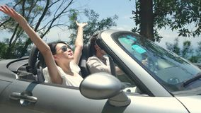 Asian couple having fun driving and riding in convertible sport car