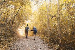 Asian couple hipster . Asian couple hipster hiking on mountain holiday wild adventure  in autumn forest park . Helping ,helps ,business sucess and team work royalty free stock image