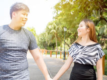 Asian couple holding hands and taking a walk in the green nature Royalty Free Stock Photo