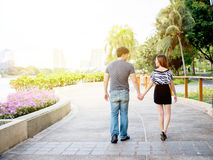 Asian couple holding hands walking in the park Royalty Free Stock Photos