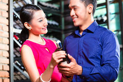 Asian couple holding wine bottle in restaurant Royalty Free Stock Photography