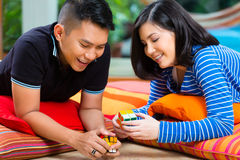 Asian couple at home playing with magic cube Royalty Free Stock Image