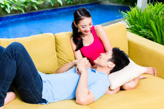 Asian couple huddling on sofa in living room of home stock image