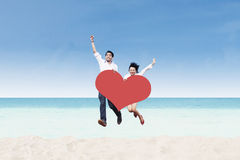 Asian couple jumping on beach with heart card Royalty Free Stock Images