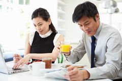 Asian Couple With Laptop And Newspaper At Breakfast Stock Photography