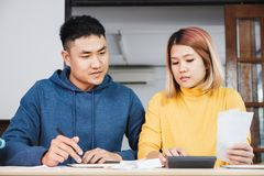 Asian couple list home financial bill budget on table in kitchen royalty free stock photography