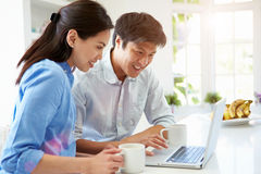 Asian Couple Looking at Laptop In Kitchen. Holding Hot Drink Stock Photos