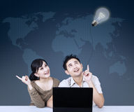Asian couple looking at lightbulb on blue Stock Images