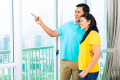 Asian couple looking out of apartment window Stock Photo