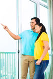 Asian couple looking out of apartment window Stock Image