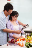 Asian couple looking at USG fetus picture. In the kitchen Royalty Free Stock Images