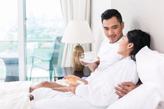 Asian couple lounging in bed at morning Royalty Free Stock Photos
