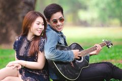 Asian couple in love. Playing acoustic song  guitar sitting on grass in the park Royalty Free Stock Image