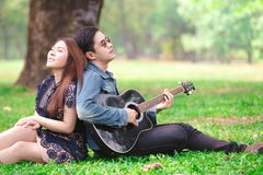 Asian couple in love. Playing acoustic song  guitar sitting on grass in the park Stock Image