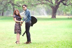 Asian couple in love. Playing acoustic song  guitar sitting on grass in the park Royalty Free Stock Photo