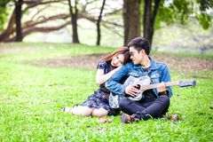 Asian couple in love. Playing acoustic song  guitar sitting on grass in the park Royalty Free Stock Photos
