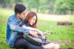 Asian couple in love. Playing acoustic song  guitar sitting on grass in the park Royalty Free Stock Photography