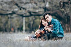 Asian couple in love. Playing acoustic ukulele song sitting on grass in the park Royalty Free Stock Photos