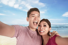 Asian couple in love making selfie photo with blue ocean as back Royalty Free Stock Image