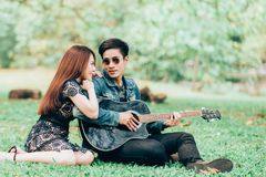 Asian couple in love. Playing acoustic song  guitar sitting on grass in the park Stock Photos