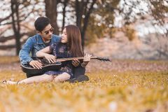Asian couple in love. Playing acoustic song  guitar sitting on grass in the park Stock Photography