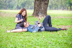 Asian couple in love. Playing acoustic song  guitar sitting on grass in the park Stock Photo
