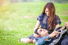 Asian couple in love. Playing acoustic song  guitar sitting on grass in the park Royalty Free Stock Images