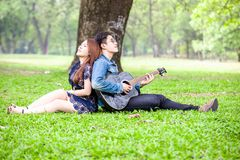 Asian couple in love. Playing acoustic song  guitar sitting on grass in the park Stock Images