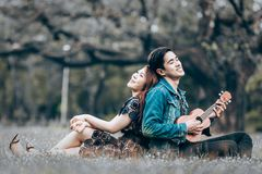 Asian couple in love. Playing acoustic ukulele song sitting on grass in the park Royalty Free Stock Photo