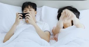 Asian couple lying on bed, man using mobile phone. Asian couple lying on bed, man using mobile phone, girlfriend stretched and hang the head on his shoulder stock footage