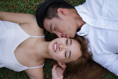 Asian couple lying on grass Stock Photo