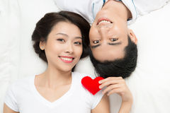 Asian couple lying holding heart shape Royalty Free Stock Photography