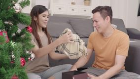 Asian couple man giving christmas gifts to his girlfriend in their living room at home in Christmas Festival. Lifestyle woman and man happy celebrate summer stock video