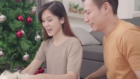 Asian couple man giving christmas gifts to his girlfriend in their living room at home in Christmas Festival. Lifestyle woman and man happy celebrate summer stock video footage