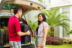 Asian couple packing car for holiday. Asian couple packing car with suitcases for holiday and smiling Royalty Free Stock Photo