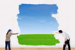 Asian couple paint outdoor field. With blue sky and green grass Royalty Free Stock Photos
