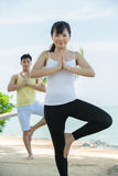Asian couple performing yoga. Stock Photo