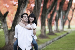 Asian couple piggy back. Portrait of happy young couple playing around in the nature on autumn day Royalty Free Stock Photography