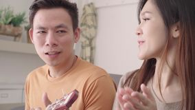 Asian couple playing guitar and singing together in living room at home, sweet couple enjoy love moment. stock video