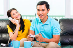 Asian couple playing video games and phone. Young Asian handsome couple having leisure time together and playing with laptop video game console and phone on Royalty Free Stock Photo