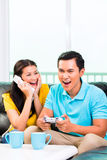 Asian couple playing video games and phone. Young Asian handsome couple having leisure time together and playing with laptop video game console and phone on Royalty Free Stock Image