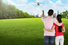 Asian couple pointing propeller plane Stock Photo