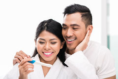 Asian couple with pregnancy test in bed. Asian women surprising her husband with positive pregnancy test, he seems reasonably pleased stock image